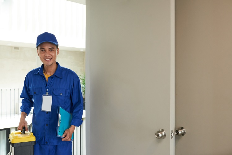 Smiling young handyman with toolbox entering home